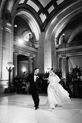 black and white photo of bride and groom preparing for first dance at wedding reception