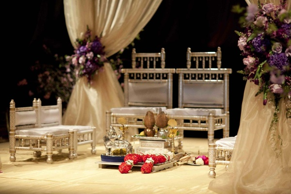 Hindu wedding mandap with golden chairs and cream cushions