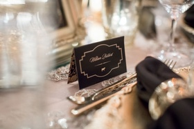 Black and gold place card with menu selection icon cow on escort card tent format