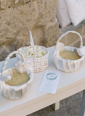 outdoor wedding white baskets filled with flower petals and dried rice ceremony program with wreath