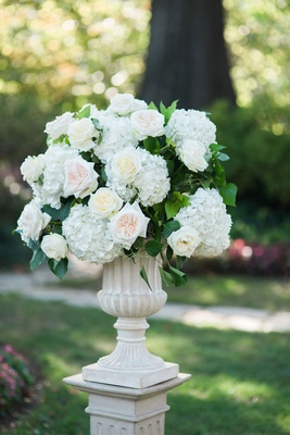 Stone urn on riser ceremony decoration outdoor wedding with white hydrangea pink rose ivory rose