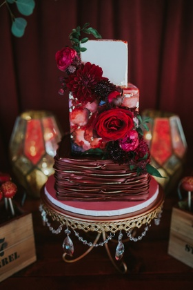 small three-tier wedding cake with water color tier and vampy colors