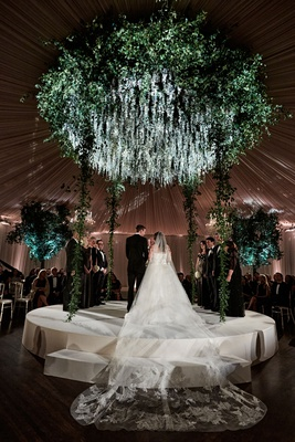 bride in strapless wedding dress and cathedral veil on raised round stage ceremony wedding greenery