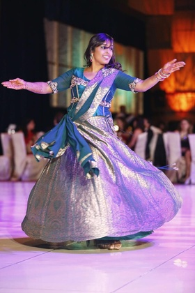 Indian bride dances at reception in a silver and blue lehenga