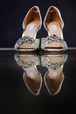 Silver wedding shoes on mirror table with peep toe