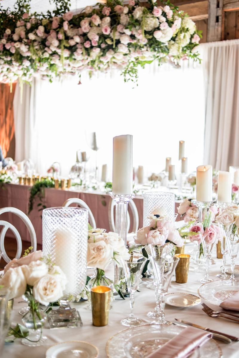 reception tables with pillar candles in textured hurricanes and on stands