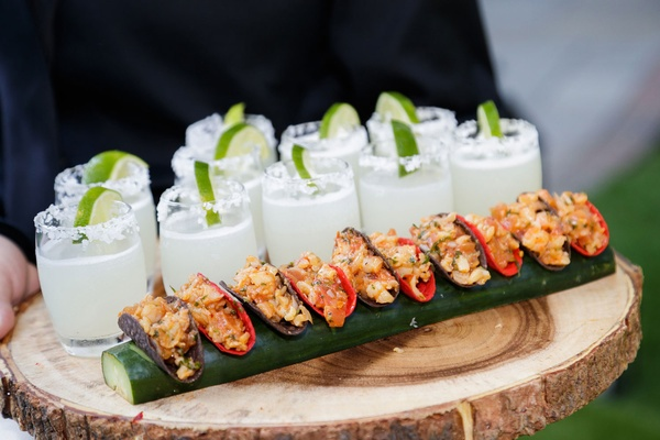 Wood slice tray with mini tacos and margaritas with salt and lime at outdoor cocktail hour
