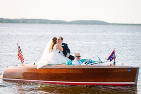 bride and groom kiss on small motor boat on the water