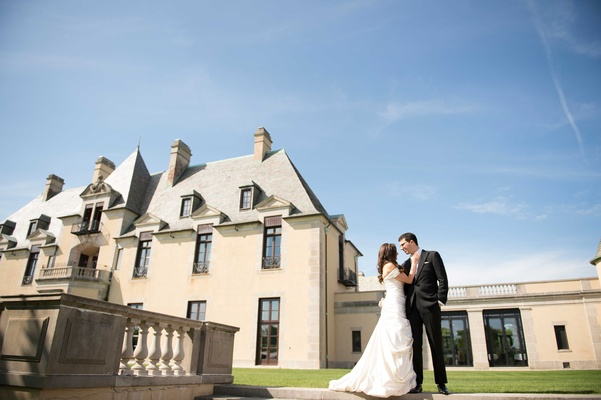 Bride in Pnina Tornai wedding dress and groom in tuxedo in front of Oheka Castle