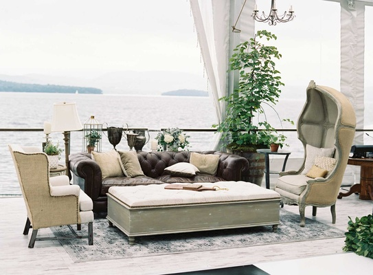 Dark leather chesterfield sofa with antique armchairs and large ottomans lake house wedding