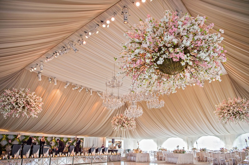 Large reception ballroom white dance floor with chandeliers draped ceiling and flower chandeliers
