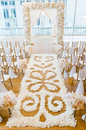 White, blush, gold wedding ceremony decorations with intricate flower petal pattern aisle runner
