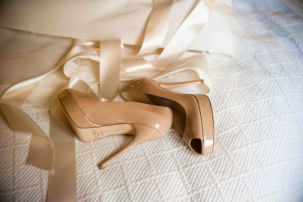 Jimmy Choo nude peep toe pump on white comforter