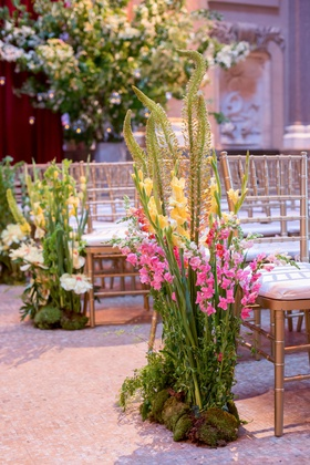 Wedding ceremony gold chairs flowers pink yellow greenery growing from ground