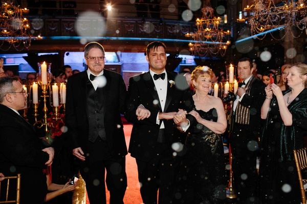 Matthew Christopher, couture wedding gown designer, in black tuxedo walks down the aisle