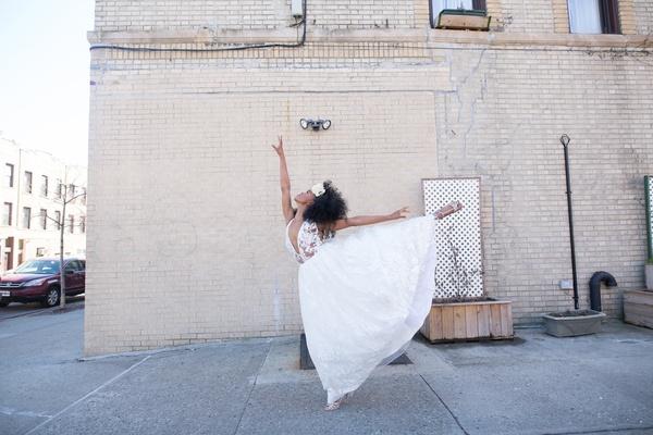 bride in pantora bridal wedding dress with plunging neckline in ballet pose