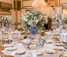ballroom wedding reception round table gold chairs charger plates blue white chinoiserie vase white