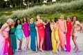 Ladies at a wedding dressed in a variety of colorful dresses