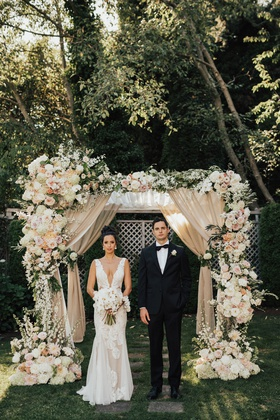 bride and groom under chuppah drapery white pink peach flowers greenery plunging v neck gown
