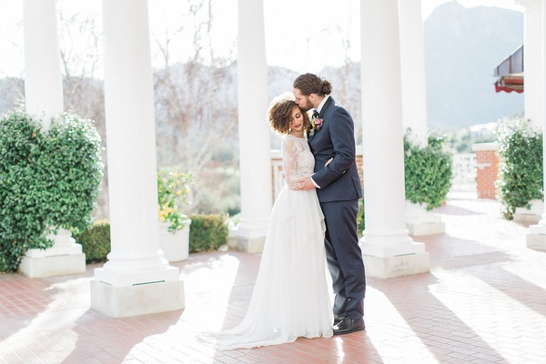 bride in long sleeve wedding dress and groom in man bun at sherwood country club