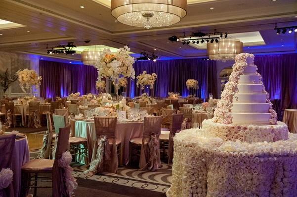 Round guest tables in ballroom next to wedding cake