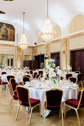 wedding reception burgundy and gold velvet chairs greenery white flower centerpieces chandeliers