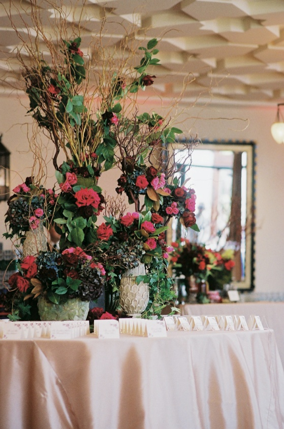 Branches and flowers in vintage vases on table