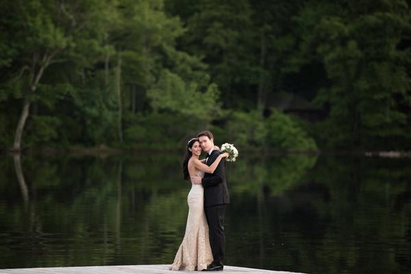 groom in Ermenegildo Zegna hugs bride in mark ingram blush wedding dress in front of lake
