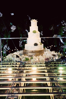 5-tier wedding cake with succulent accents on floating display