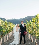 bride in jim hjelm wedding dress and groom stand in vineyard vines california red bouquet of flowers