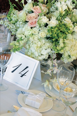 Table number in front of centerpiece with white and pink flowers
