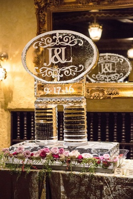 Wedding reception ice sculpture with flowers greenery pink roses wedding date and monogram