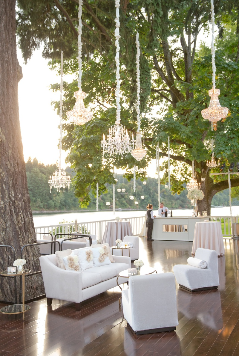 River porch wedding lounge with couches and chandeliers in tree