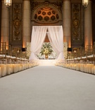Wedding ceremony white aisle runner candles along side hurricane white chuppah flower wall
