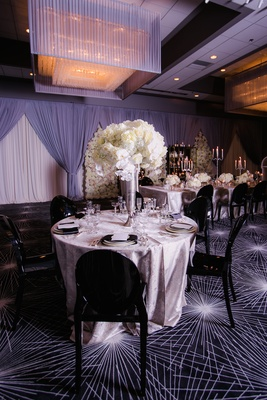 Wedding reception at The Estate by Gene & Georgetti with black ghost chairs, silver linens