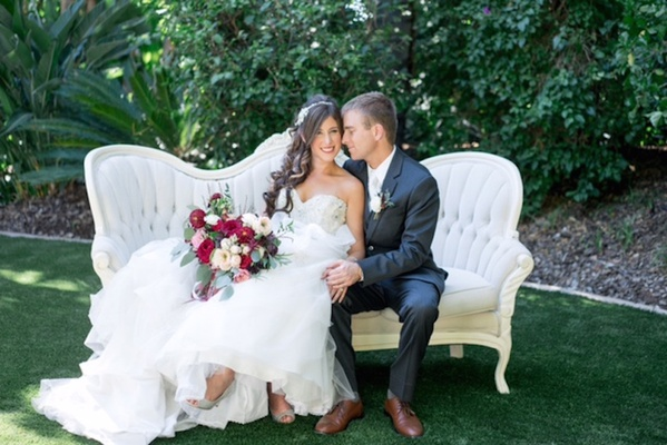bride in alfred angelo gown, groom in dark navy grey suit from the black tux sit on fancy loveseat