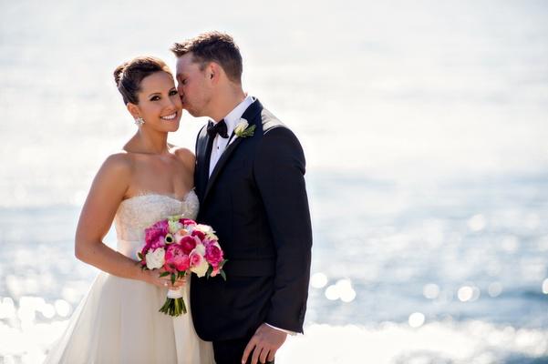 Groom kisses bride's cheek in front of Ocean at Terranea Resort