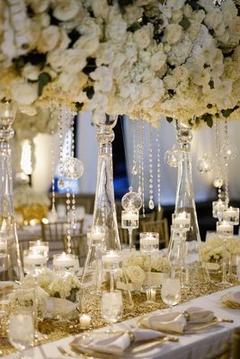 Wedding reception table with tall centerpiece of white hydrangeas, roses, orchids, floating candles