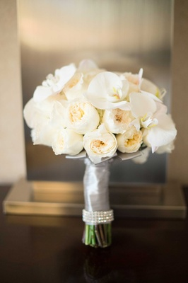 Off-white peonies and orchids in crystal-rimmed ribbon