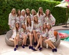 Wedding party bridesmaids in robes flower print and bright blue velvet slippers by pool at la quinta