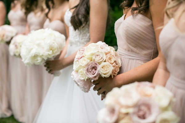 Bridesmaids holding bouquets of pink rose, cafe au lait dahlia, peony flowers and bride with peonies