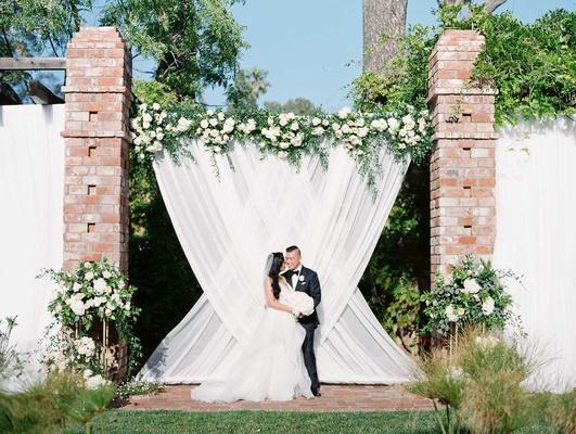wedding ceremony white drapes bride groom portrait altar greenery white pink flowers