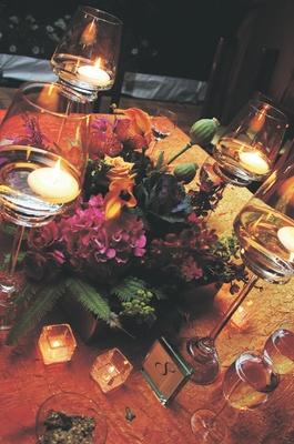 Wedding reception table decorated with fuchsia and orange flowers in a wood box surrounded by candle