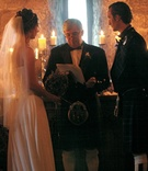 Bride and groom at altar in stone candlelit castle room