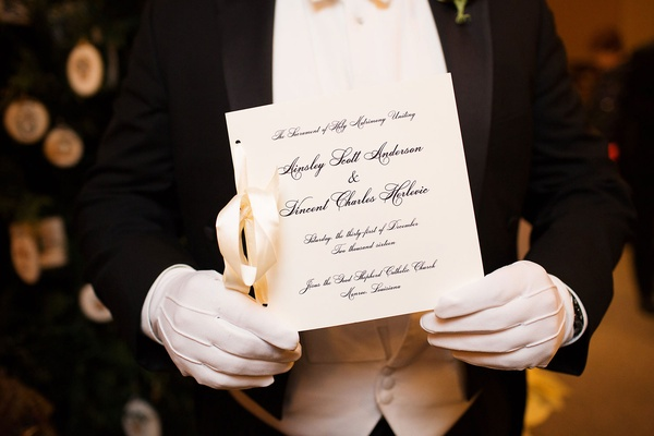 Man in white gloves holding formal ceremony program white stationery and black calligraphy ribbon