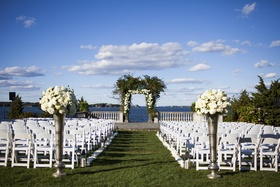 outdoor ceremony set up overlooking atlantic ocean lawn chairs tall vases floral arch