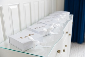 White box with white ribbon gold calligraphy names on top of box on white gold dresser