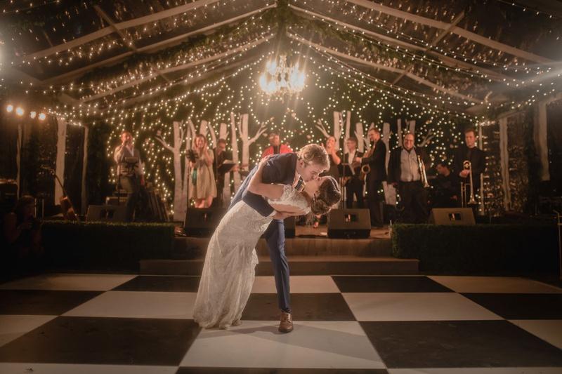 wedding photo of bride in keyhole back wedding dress dip string lights checkerboard dance floor