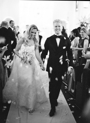 black and white photo of bride and groom leaving church ceremony flower petals thrown by guests
