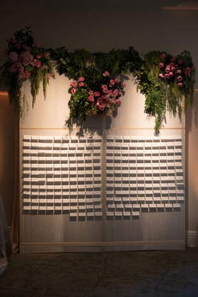 Wedding reception cocktail hour escort card display wall pink roses greenery on top